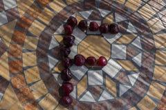 Letra F hecha con los cherrys para formar una letra del alfabeto con las frutas Fotos de archivo libres de regalías