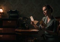 Letra hermosa de la lectura de la mujer en interior retro fotos de archivo libres de regalías