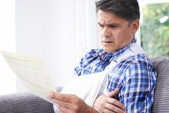 Letra madura da leitura do homem sobre ferimento fotos de stock
