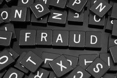 A letra preta telha a soletração da palavra & do x22; fraud& x22; fotografia de stock