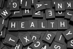 A letra preta telha a soletração da palavra & do x22; health& x22; Foto de Stock