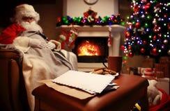 Letra a Santa Claus perto do presente e das velas Fotografia de Stock Royalty Free