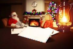 Letra a Santa Claus perto do presente e das velas Fotografia de Stock