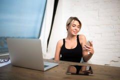 Letra sonriente del email de la lectura de la secretaria en el teléfono móvil durante trabajo sobre el ordenador portátil imagen de archivo