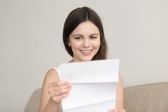 Letra sorprendida de la lectura de la mujer con las buenas noticias inesperadas, feelin Fotografía de archivo