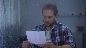 Letra triste detrás de la ventana lluviosa, pago vencido, pobreza de la lectura del hombre del crédito de banco almacen de metraje de vídeo
