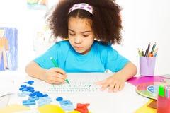 Letras africanas de uma escrita da menina com lápis foto de stock