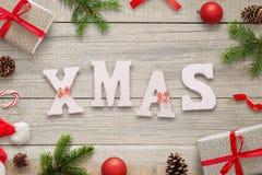 Letras blancas de Navidad en la tabla de madera rodeada con las decoraciones de la Navidad, los regalos, las ramas del abeto, las Imagen de archivo libre de regalías