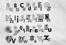 26 letras blancos y negros del periódico Imagenes de archivo