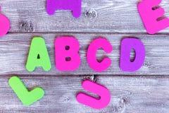 Letras coloridas A, B, C, D y otras en fondo de madera blanqueado imagenes de archivo