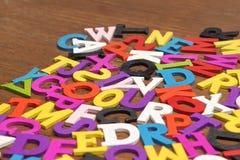 Letras coloridas de madeira inglesas no fundo da madeira de Brown Imagens de Stock Royalty Free