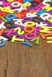 Letras coloridas de madeira inglesas no fundo de madeira vertical Fotos de Stock