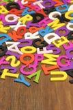 Letras coloridas de madeira inglesas no fundo de madeira vertical Fotos de Stock Royalty Free