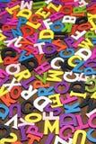 Letras coloridas de madeira inglesas no fundo de madeira vertical Fotografia de Stock Royalty Free