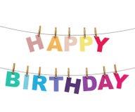 Letras coloridas do feliz aniversario que penduram na corda com os pregadores de roupa, isolados no branco Fotografia de Stock