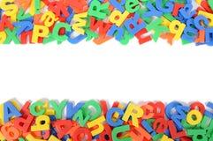 Letras da beira plástica do alfabeto do brinquedo no fundo branco, espaço da cópia Fotos de Stock Royalty Free