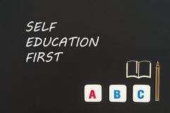 Letras de ABC y miniatura del conglomerado en la pizarra con la educación del uno mismo de las palabras primero Imagen de archivo