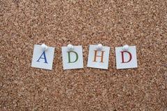 Letras de ADHD fixadas a um quadro de mensagens da cortiça Fotografia de Stock