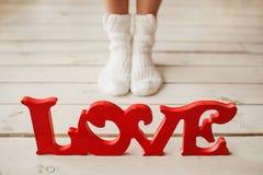 Letras de amor en el piso de madera con las piernas de la mujer Imagen de archivo libre de regalías