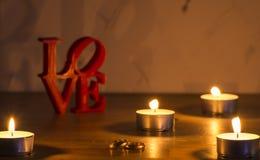 Letras de amor rojas en el fondo blanco en la izquierda con dos anillos y velas imagenes de archivo