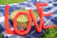 Letras de amor sobre una manta de la comida campestre y una cesta Fotos de archivo libres de regalías