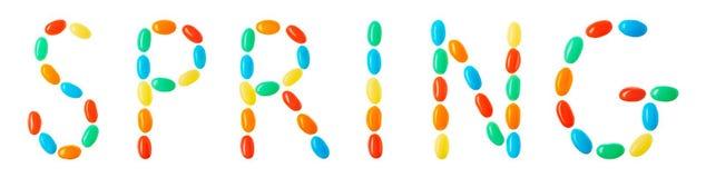Letras de la primavera hechas de los caramelos multicolores aislados en blanco Fotografía de archivo