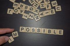 Letras de la teja con la mudanza de la mano imposible a posible en un fondo negro con las letras mezcladas en el top Negocio del  foto de archivo