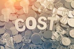 Letras de madeira do close up da palavra do custo com o montão das moedas Imagem de Stock