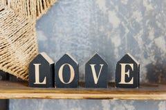 Letras de madeira que formam a palavra AMOR escrito no fundo concreto fotos de stock royalty free