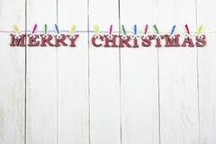 Letras de madeira, vermelhas com um cumprimento do Natal em um fundo branco Imagens de Stock