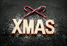 Letras de madera de 'Navidad', azúcar como nieve y bastones de caramelo rojos en negro Imagenes de archivo