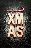 Letras de madera de 'Navidad', azúcar como nieve y bastones de caramelo rojos en negro Foto de archivo