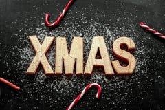 Letras de madera de 'Navidad', azúcar como nieve y bastones de caramelo rojos en negro Fotos de archivo