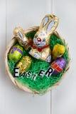 Letras de Pascua, conejitos del chocolate y huevos en una cesta Imágenes de archivo libres de regalías