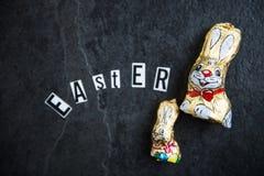 Letras de Pascua y conejitos del chocolate en fondo oscuro Imagen de archivo libre de regalías