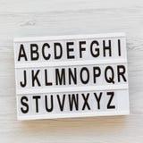 Letras de A a Z Alfabeto inglés en tablero moderno sobre la superficie de madera blanca, visión de arriba De nuevo a concepto de  imagen de archivo