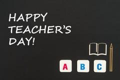 Letras del ABC y miniatura del conglomerado en la pizarra con día feliz del ` s del profesor del texto Foto de archivo