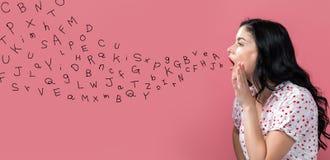 Letras del alfabeto con el discurso de la mujer joven imágenes de archivo libres de regalías