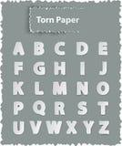 Letras del alfabeto en el papel rasgado Fotos de archivo