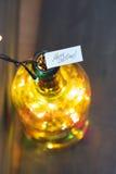 Letras del día de fiesta, Feliz Navidad, y botella con una guirnalda Imágenes de archivo libres de regalías