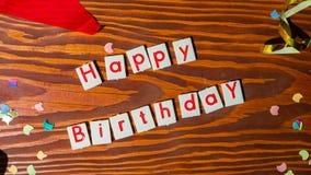Letras del feliz cumpleaños con la decoración del partido en fondo de madera