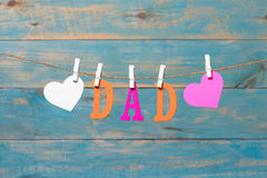Letras del PAPÁ Mensaje del día de padres con los corazones que cuelgan con las pinzas sobre el tablero de madera azul Imágenes de archivo libres de regalías