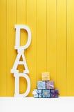 Letras del texto del PAPÁ con las cajas de regalo en fondo de madera amarillo Imágenes de archivo libres de regalías
