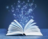 Letras do alfabeto em torno do livro aberto foto de stock royalty free