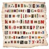 Letras do alfabeto feitas do jornal, compartimento fotografia de stock royalty free