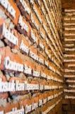 Letras do cartão em uma parede de tijolo vermelho Imagens de Stock