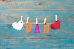 Letras do PAIZINHO Mensagem do dia de pais com os corações que penduram com os pregadores de roupa sobre a placa de madeira azul Fotos de Stock