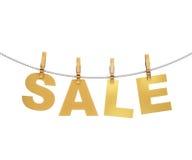 Letras douradas da venda que penduram na corda com os pregadores de roupa, isolados no branco Fotos de Stock Royalty Free