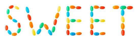 Letras dulces hechas de los caramelos multicolores aislados en blanco Fotografía de archivo libre de regalías