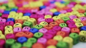 Letras en la tabla, letras coloreadas de giro en una tabla blanca almacen de video
